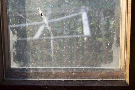 Very dirty window glass with a cobweb with a wooden frame