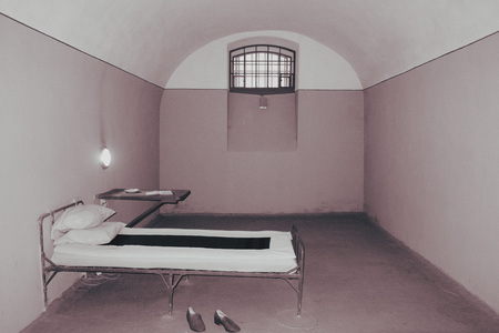 Old prison cell, bed and table 写真素材