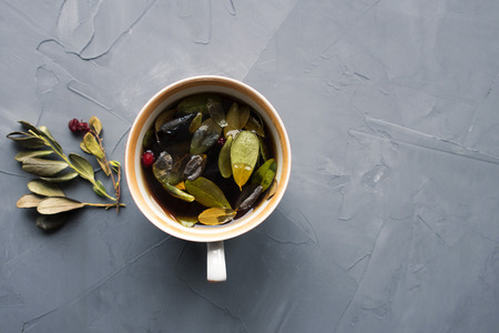 Lingonberry tea and leaves close-up on a gray background