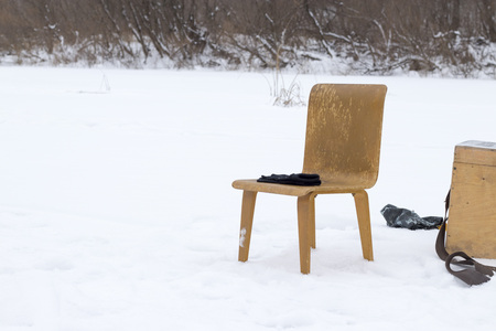 Chair and wooden box in the snow, in winter in nature.