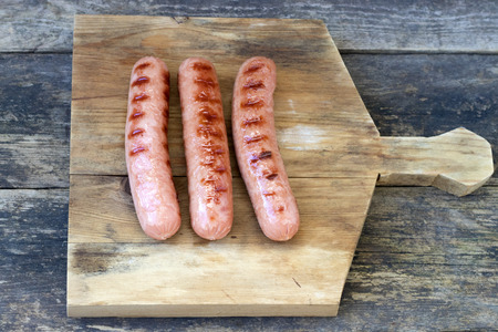 Grilled sausages located on a cutting board which is located on an old wooden background in rustic style 版權商用圖片