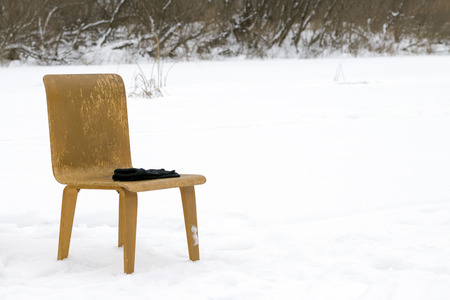 Wooden chair and on the snow, in winter in nature.