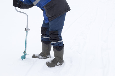Fisherman makes a hole auger ice screw in winter 版權商用圖片