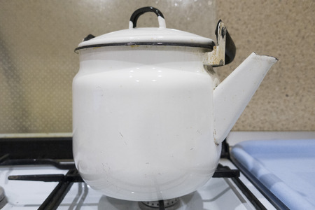 Old iron kettle on the stove, closeup. 版權商用圖片