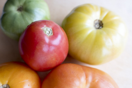 Tomatoes of different colors, red, orange, yellow, green, close-up.