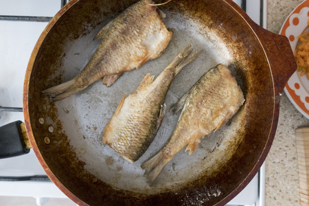 The process of cooking fried fish in a pan, close-up. Stockfoto