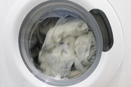 Washing machine drum with rotating laundry, close-up.