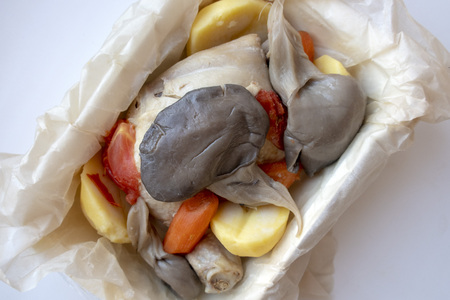 Cooked oyster mushroom with chicken and vegetables on a light background, close-up.