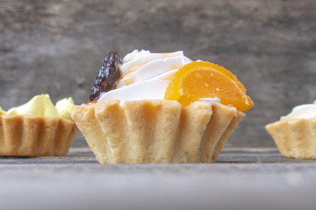 Beautiful shortbread cakes with cream and marmalade on a wooden background. Banco de Imagens