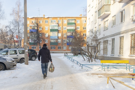 Winter morning, a man goes with a garbage bag, December 2, 2018, Russia, the city of Sterlitamak, Salavat Yulaev street 6.