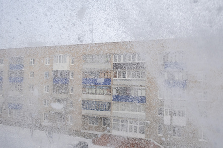 Abstract image of a snowfall and a building behind the snow