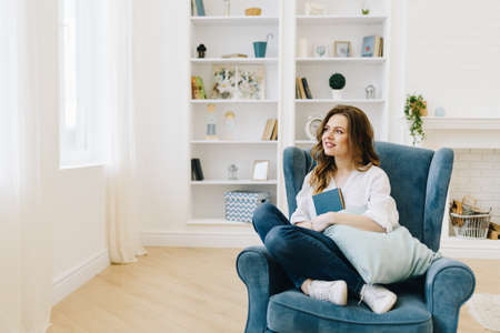 Young beautiful woman in an armchair with a book, relaxing in cozy living room Banco de Imagens
