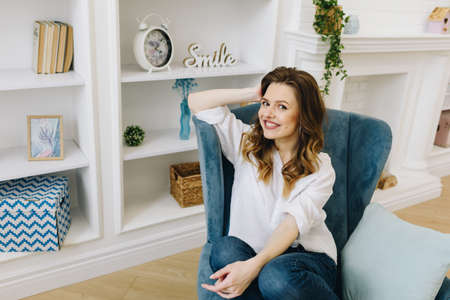 Relaxed cheerful happy woman in an armchair wearing jeans