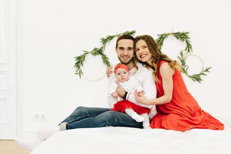 Beautiful caucasian family of three on bed