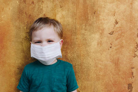 Caucasian child wearing medical protective mask on his face during the global coronavirus covid-19 virus pandemic Banco de Imagens