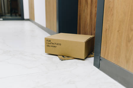 Contactless delivery box on doormat next to front door, package ordered online during global coronavirus covid-19 infection pandemic as digital transformation changes e-commerce