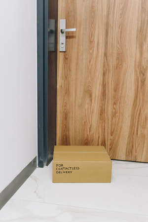 Vertical image of box delivered via contactless delivery on doormat in front of front door,parcel ordered online during global coronavirus covid-19 infection global pandemic and digital transformation Banco de Imagens - 144868510