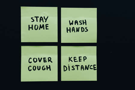 Four official who preventive measures on sticky notes isolated on deep black background: wash hands, cover cough, stay home and keep distance in the global coronavirus covid-19 pandemic