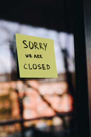 Note or sign on front door of a shop, restaurant or other small business saying