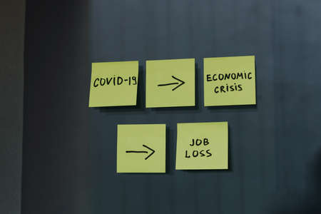 Effect of covid-19 corona virus on economic crisis and recession, and on unemployment, job loss and economic situation, post it notes on dark background Banco de Imagens
