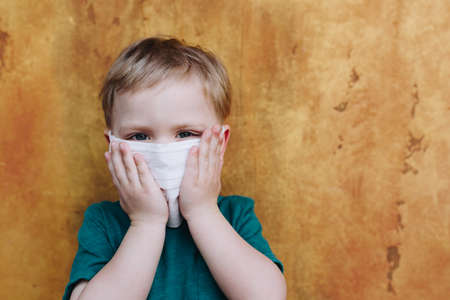 Cute small caucasian boy wearing protective medical mask on face during the global coronavirus covid 19 virus pandemic