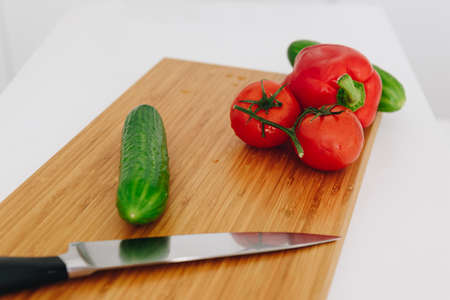 Bell pepper, tomatoes, cucumbers on a chopping board with a knife ready for cooking