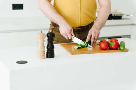 Close up of hands caucasian young man in yellow cooking healthy vegetables for salad in modern kitchen with knife Banco de Imagens