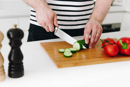 Close up of hands of caucasian man cooking a nice healthy vegetable meal or salad in a modern kitchen with a knife