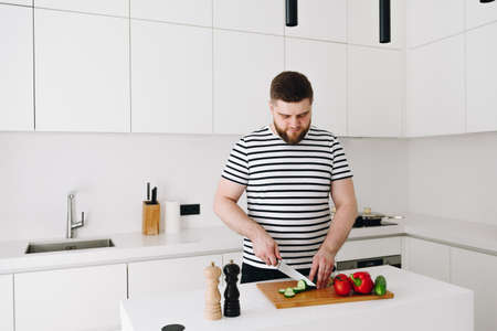 Handsome young caucasian man cooking a nice healthy vegetable meal or salad in a modern bright white kitchen with a knife