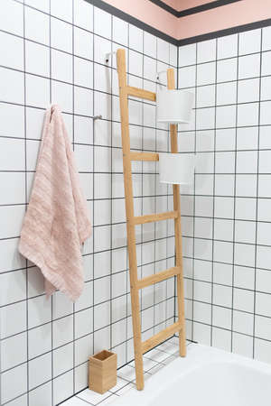 Stylish modern Scandinavian loft bathroom interior: pretty white square tiles, towel rack, storage containers and cotton towel Banco de Imagens