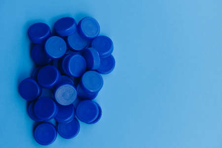 Pile of blue plastic caps from bottles isolated on blue background, concept of ocean plastic waste and pollution problem, part of the global warming and climate change crisis