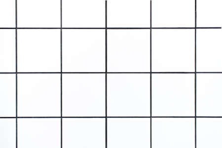Closeup shot of small white square tiles with black grout lines, close up of tiled bathroom wall as a geometric graphic background or backdrop