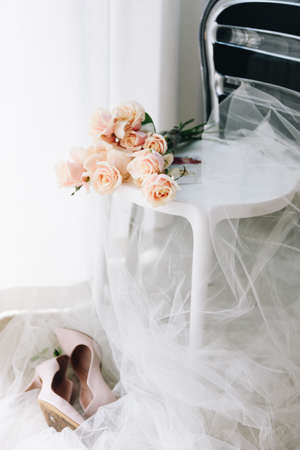 Feminine picture of bride getting ready in the morning of her wedding: beautiful bouquet of roses on a chair with veil, pair of bridal wedding shoes