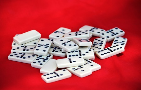 Beautiful dominoes close up over bright red background Stock Photo