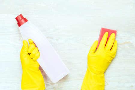 Floor cleaning concept. Gloves, sponge and bottle on wooden background.