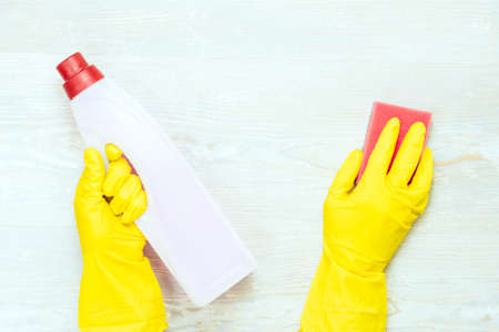 Floor cleaning concept. Gloves, sponge and bottle on wooden background.