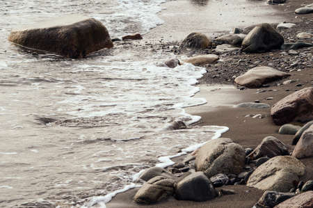 Beautiful natural landscape. Sea water covers the beach. Wet stones. Brown color.