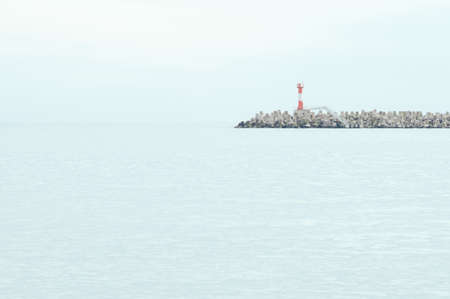Tower of the lighthouse on the breakwaters. Beautiful background landscape with blue sea and sky.