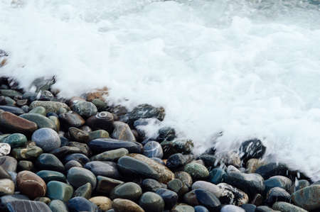 White wave washing the stones of the shore. Beautiful background with beach of stone.