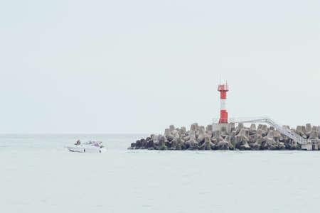 Lighthouse on breakwaters. Boat floating on the waves. Horizontal beautiful background image 免版税图像