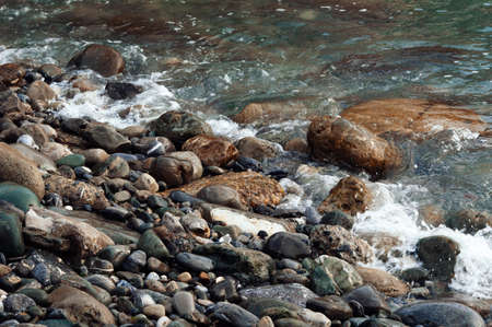 The sea wave is washed by colored stones.Background with beautiful wet stones and water.