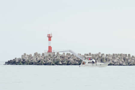 A boat floating past breakwaters. Beautiful gray background