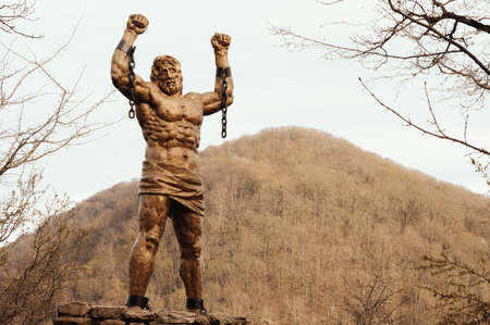 Statue of Prometheus against the background of the mountain. Gold tone. 免版税图像
