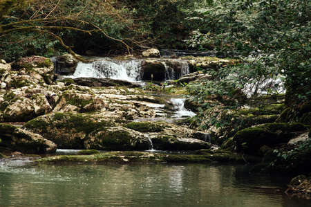 Cascade of a mountain river. Stones covered with moss. Beautiful background. 免版税图像