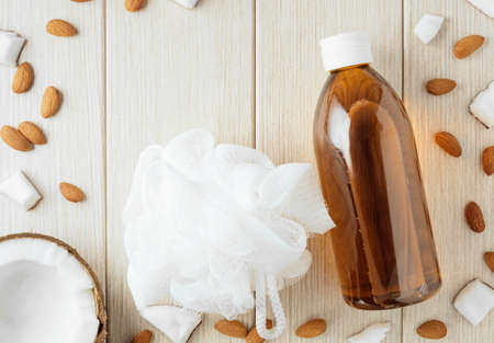 Composition with plastic bottle and mesh shower sponge for body care and beauty products. Beautiful background with almond and coconut.