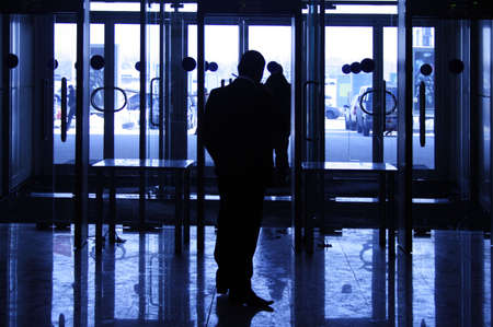 The security guard provides safety on an entrance in large business center photo