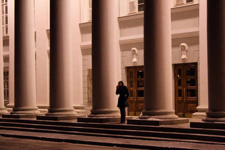lonelyness: girl - student at the entrance in university between pillars wait the car Stock Photo