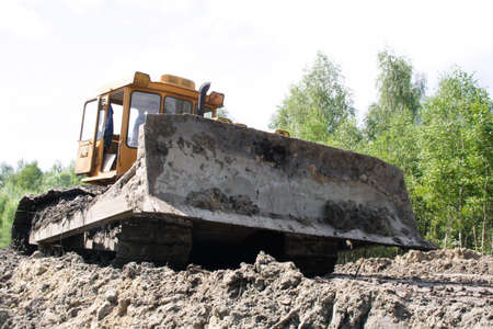 A large bulldozer working on the forest. Shot from a low angle. photo