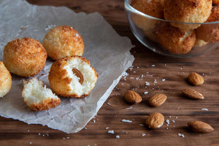 Coconut balls with almonds lie on a wooden table. The cookies are broken into pieces. Reklamní fotografie