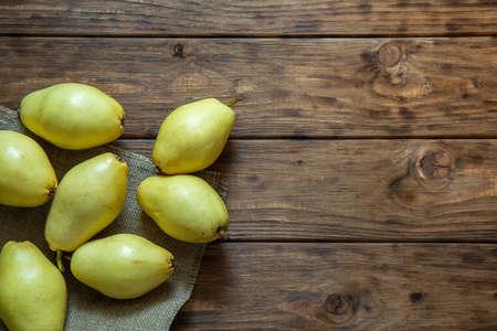 Gelbe Birnen liegen auf einem hölzernen Hintergrund.